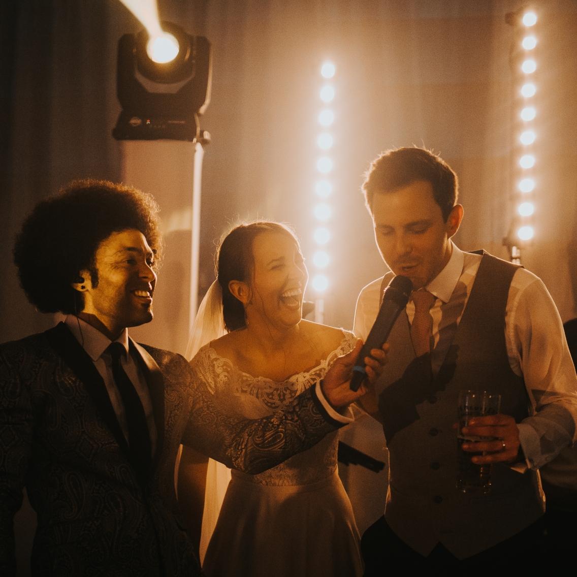 Groom singing on stage at wedding