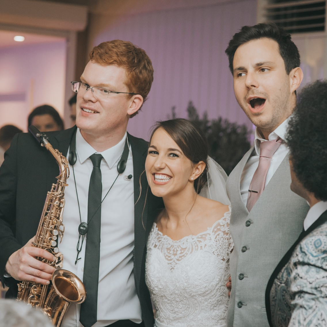 Bride and groom with saxophonist and lead singer
