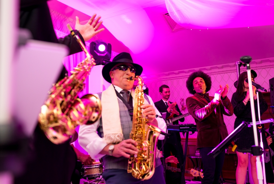 Guest plays saxophone during wedding party